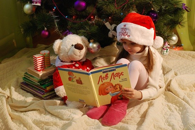 holčička si čte knížku u vánočního stromu